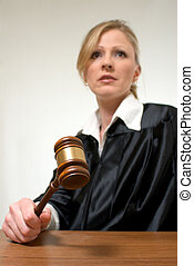 Female judge - Blond woman judge holding a gavel with...
