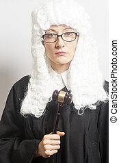Female judge wearing a wig and Back mantle with eyeglasses holding judge gavel