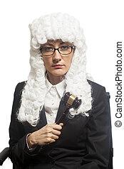 Female judge wearing  wig and  mantle with eyeglasses holding judge gavel
