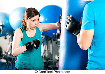 Female kick boxer with trainer hitting sandbag