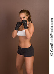 Female kick boxer working out - Woman in boxing gloves