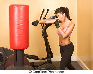 Female kickboxing exercise - Attractive woman kickboxing...