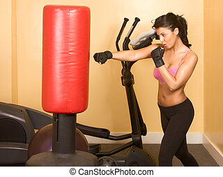 Attractive woman kickboxing with red punching bag