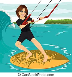 Female kiteboarder enjoys surfing waves with kiteboard -...