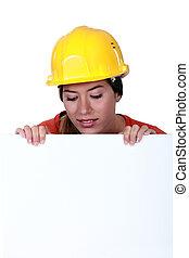 Female laborer behind white sign