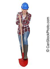 Female laborer digging with a shovel, studio shot