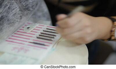 Female lashmaker work on tablet making bundles. Closeup.