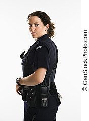 Portrait of mid adult Caucasian policewoman standing with hand on gun holster looking over shoulder at viewer.