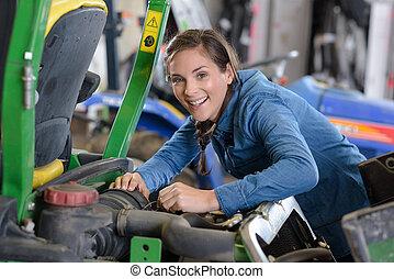 female lawn mower mechanic smiling