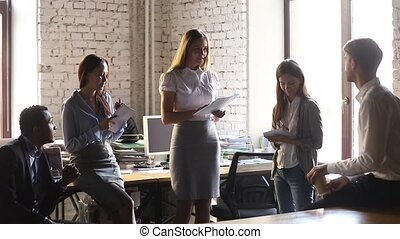 Female leader coach executive holding paper report talk instructing team workers explain paperwork at group office meeting delegates work, mentor teaching interns, manager speak at corporate training