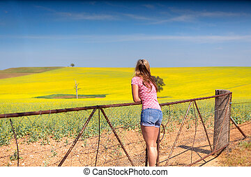 Female leaning on farm gate looks over rolling hills farmlands of golden canola