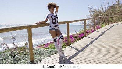 Female leaning on fencing of sidewalk - Smiling female...