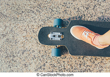 Female leg on longboard. - Female leg wearing in sneaker on...