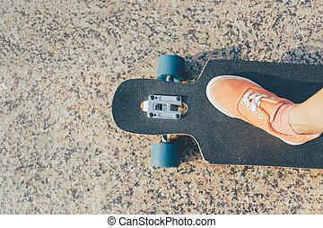Female leg on longboard. - Female leg wearing in sneaker on...