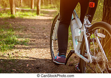 Female leg on the pedal of the bicycle