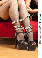 female legs and chain - young woman sitting on the couch...