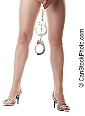 Female legs and hand holding handcuffs - A pair of long...
