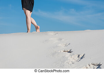 Female legs and prints on white sand
