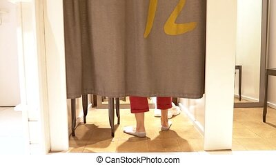 female legs are visible from under the curtains in the fitting room of a clothing store