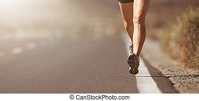 Female legs close up of a woman running on a road