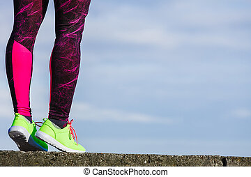 Female legs feet in vivid color yellow shoes on seaside.