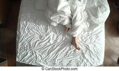 female legs in bed view from above, white bedding, 4k.
