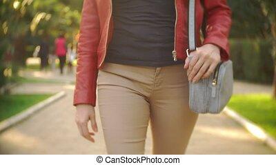 female legs in beige trousers. zhshchina with a denim...