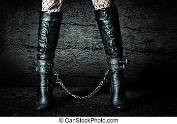 Female legs in black leather boots chained