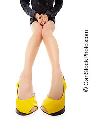 Female legs in bright yellow shoes on a white background