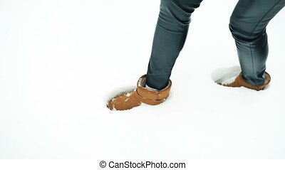 Female legs in brown uggs leave traces in the white pure snow. Slim woman wearing black leather skin-tight leggins and big flat-heeled boots with a belt puts one foot in front of the other. She is walking carefully, slowly, almost creeping. Under her weight a leggy lady showing no face makes ankle-...