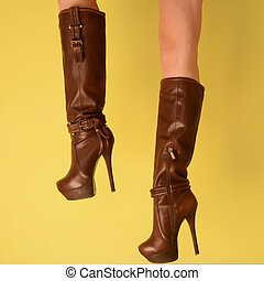 female legs in fashionable leather brown boots