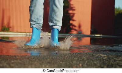Female legs in colorful gumboots are jumping in puddle on the ground enjoying autumn having fun. Happiness, outdoor activity and joyful people concept.