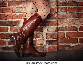Female legs in high brown leather boots