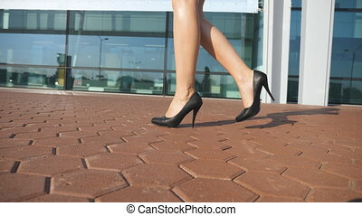 Female legs in high heels shoes walking in the urban street....