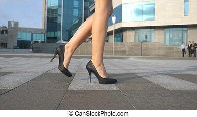 Female legs in high heels shoes walking in the urban street....