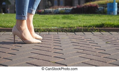 Female legs in high heels shoes walking in urban street....