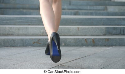 Female legs in high heels shoes walking on the stairs. Feet...
