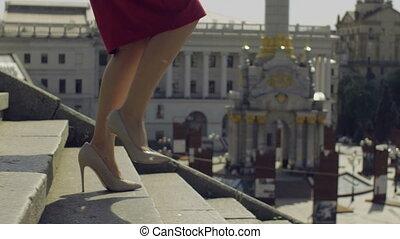 Female legs in high heels stepping down on stairway -...