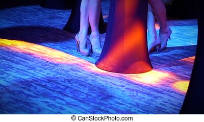 female legs in night club with colored light