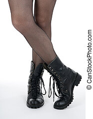 Female legs in pantyhose and black boots