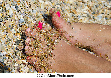 female legs in the gravel and sand beach