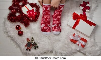 Female legs in warm socks with red white ornaments on a background of fur skin, tinsel and boxes with gifts relaxing at home. Winter holiday Christmas and New Year concept. Close up. Slow motion