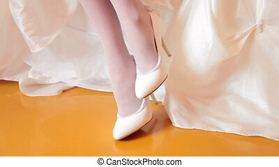female legs in white wedding shoes against white embroidered dress