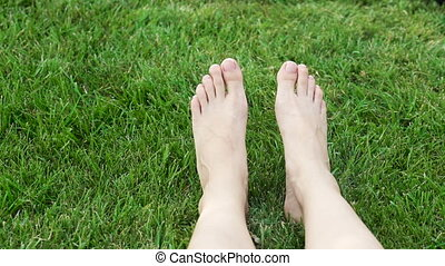 Female legs on the green grass in the park