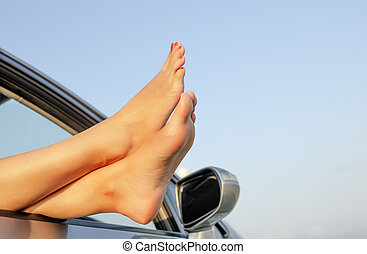 Female legs out of a car window on a background of sky.