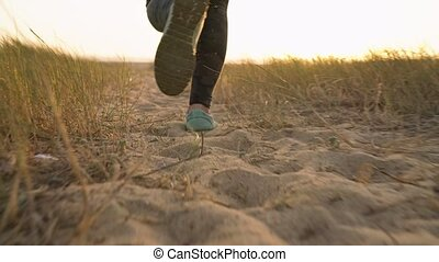 Female legs running along a sandy beach to the ocean