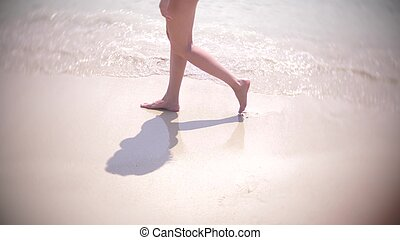 female legs running splashing into water. girl run barefoot on the sand beach.