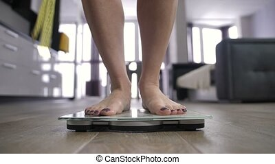 Female legs stepping on weight scale and dancing