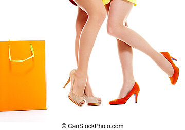 Female legs over white background with paperbag near by