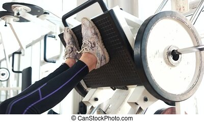 Female legs training on machine press in gym.